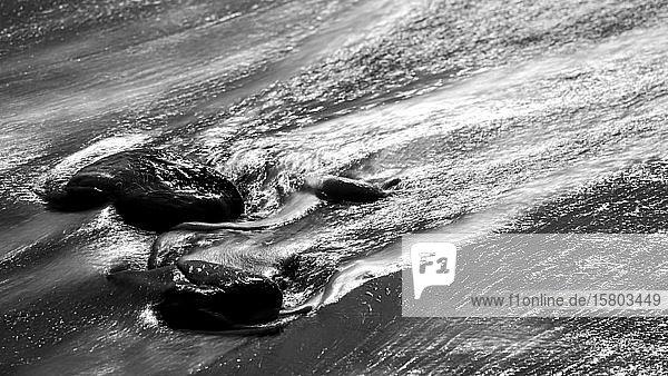 Mit Wasser umspülte Steine im schwarzen Lavasand  schwarz-weiß  La Palma  Kanaren  Spanien  Europa
