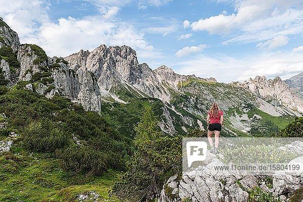 Junge Frau blickt über Landschaft  Schroffe Berggipfel  Berge  Armkarwand  Große Bischofsmütze  Salzkammergut  Oberösterreich  Österreich  Europa