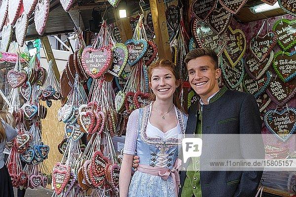 Junges Paar in Tracht vor Lebkuchenherzen  Lebkuchenstand  Wiesn  Wies´n  Oktoberfest  München  Oberbayern  Bayern  Deutschland  Europa