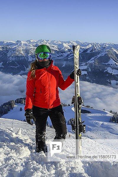 Skifahrerin mit Skihelm und Ski steht an der Skipiste  Blick in die Kamera  hinten Bergpanorama  SkiWelt Wilder Kaiser  Brixen im Thale  Tirol  Österreich  Europa