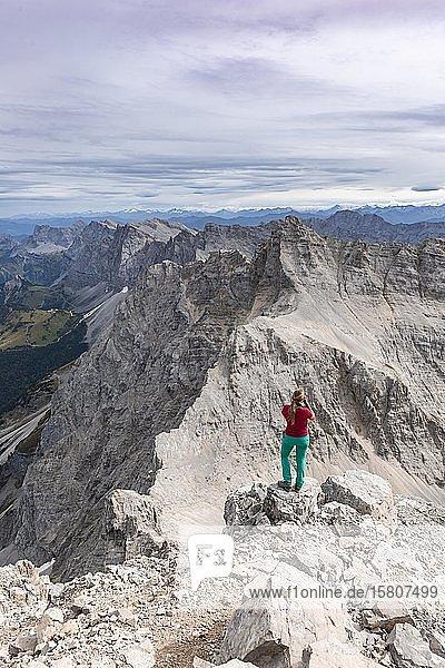 Frau steht auf Felsen und fotografiert  Blick von der Birkkarspitze  Karwendeltal  Tirol  Österreich  Europa