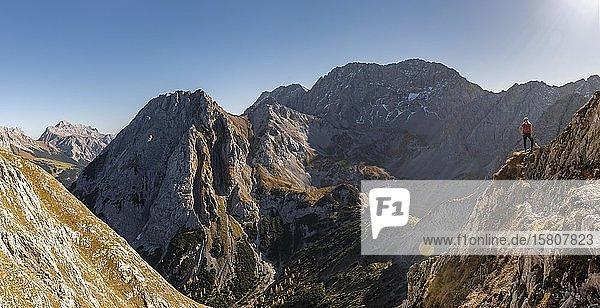 Bergsteigerin mit Kletterhelm steht auf Felsvorsprung  Wanderweg zur Ehrwalder Sonnenspitze  Ehrwald  Mieminger Kette  Tirol  Österreich  Europa
