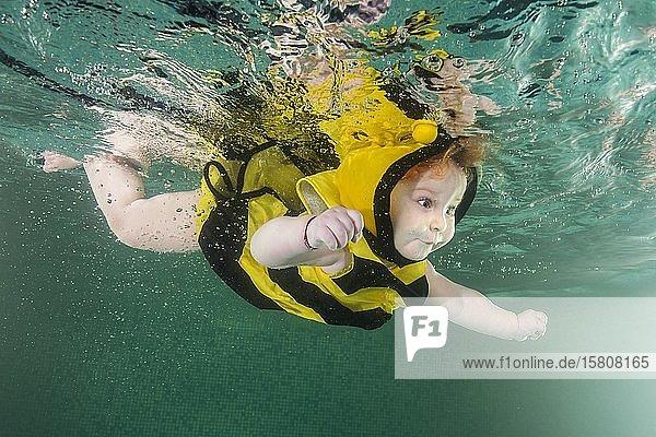 Rothaariges kleines Mädchen in Bienenkostüm schwimmt unter Wasser in einem Pool  Russland  Europa