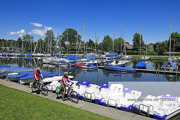 Couple with electric bikes rides in the port of Matzing on Lake Wallersee  Salzburg Lake District  Salzburger Land  Austria  Europe