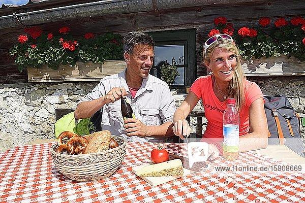 Wanderer bei der Brotzeit auf der Schreckalm  Geigelstein  Sachrang  Chiemgau  Oberbayern  Bayern  Deutschland  Europa