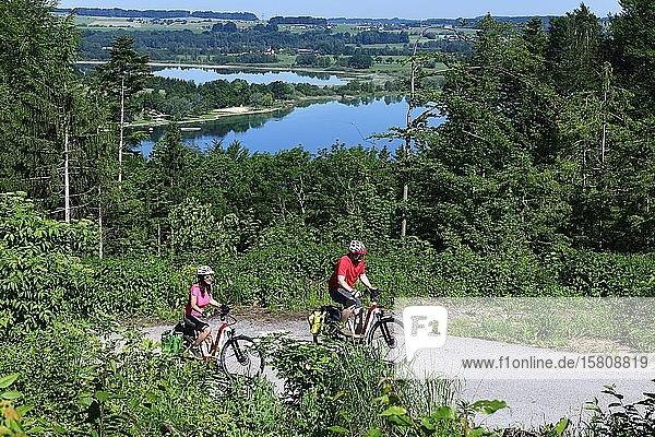 Couple with electric bikes riding above Lake Mattsee  Ramoos  Mattsee  Salzburg Lakeland  Salzburg Land  Austria  Europe