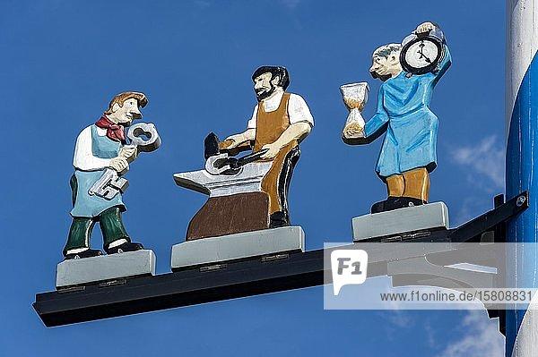 Zunftzeichen am Maibaum  symbolhafte Darstellung der Berufe Schlosser  Hufschmied und Uhrmacher  Haag in Oberbayern  Oberbayern  Bayern  Deutschland  Europa