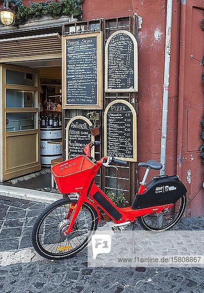 Rotes Elektro-Mietfahrrad vor einem italienischen Restaurant mit handgeschriebener Speisekarte  Rom  Italien  Europa