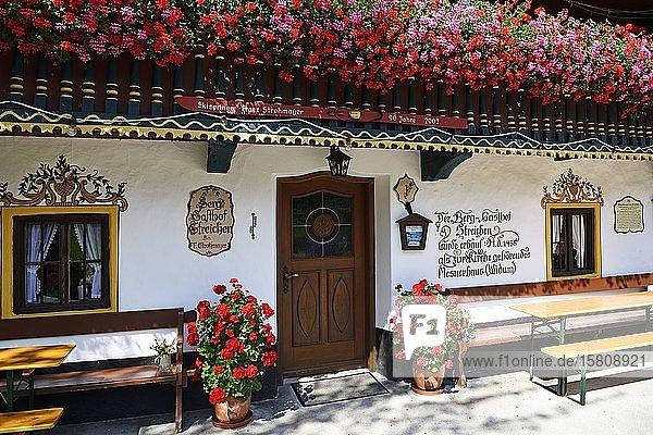 Lüftlmalerei and flowering geraniums  alpine restaurant Streichen  Schleching  Chiemgau  Upper Bavaria  Bavaria  Germany  Europe