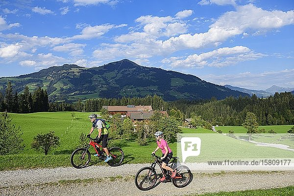 Two cyclists with electric mountain bikes on the Glantersberg with view of the Hohe Salve  Kitzbühel Alps  Tyrol  Austria  Europe