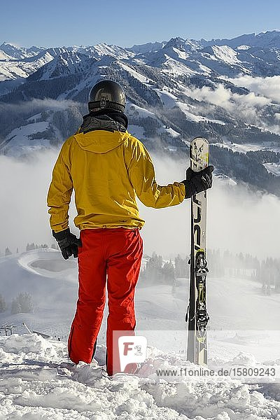 Skifahrer steht an der Skipiste und hält Ski  Blick in die Ferne  verschneites Bergpanorama  Gipfel Hohe Salve  SkiWelt Wilder Kaiser Brixenthal  Hochbrixen  Tirol  Österreich  Europa