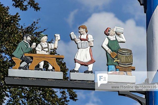 Zunftzeichen am Maibaum  symbolhafte Darstellung der Berufe Kellnerin und Gastwirt  Haag in Oberbayern  Oberbayern  Bayern  Deutschland  Europa