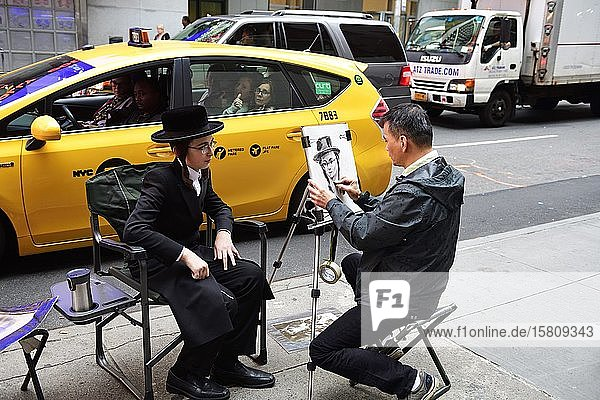A Jewish Orthodox boy with temple curls and a hat is portrayed in Times Square by a street painter  Manhattan  New York City  New York State  USA  North America