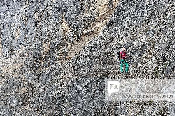 Junge Frau  Wanderin gesichert mit Kletterhelm vor einer Felswand  Klettersteig Via ferrata Francesco Berti  Sorapiss Umrundung  Dolomiten  Belluno  Italienmit Kletterhelm in einer Felswand  Klettersteig Via ferrata Francesco Berti  Sorapiss Umrundung  Dolomiten  Belluno  Italien  Europa