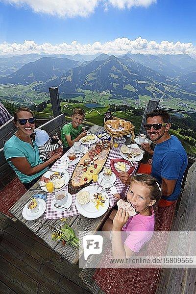 Family eating a snack at the Salvenalm  Hohe Salve  Hopfgarten  Brixental  Kitzbühel Alps  Tyrol  Austria  Europe