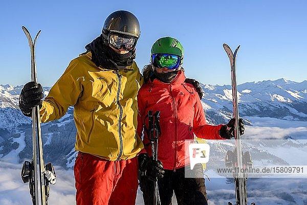 Zwei Skifahrer mit Skihelm und Ski stehen vor Bergpanorama  Paar  Blick in die Kamera  SkiWelt Wilder Kaiser  Brixen im Thale  Tirol  Österreich  Europa