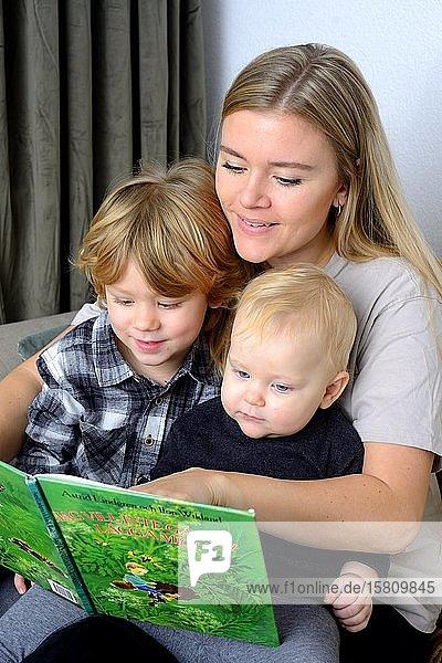 Mutter liest ein Buch mit zwei Kindern  Junge und Baby  Schonen  Schweden  Europa