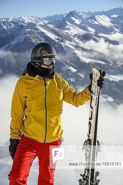 Skifahrer steht an der Skipiste und hält Ski  Blick in die Ferne  Gipfel Hohe Salve  SkiWelt Wilder Kaiser Brixenthal  Hochbrixen  Tirol  Österreich  Europa