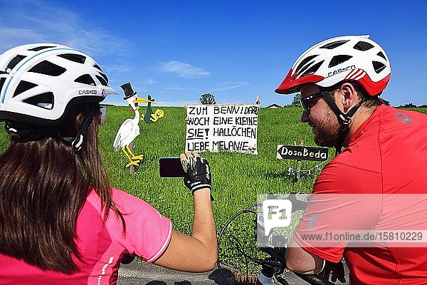 Cyclists photographing Rattling stork and banner as a welcome for a newborn child  Seeham  Salzburg Lakeland  Salzburger Land  Austria  Europe
