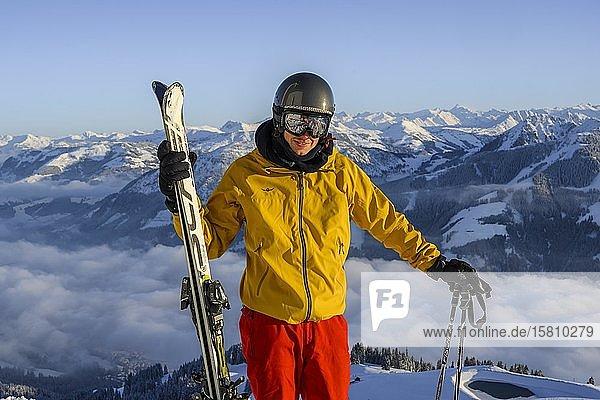 Skifahrer vor Bergpanorama  hält Ski  Blick in die Kamera  Gipfel Hohe Salve  SkiWelt Wilder Kaiser Brixenthal  Hochbrixen  Tirol  Österreich  Europa