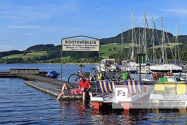 Paar mit E-Bikes pausiert auf einem Bootsteg am Obertrumer See  Obertrum  Salzburger Seenland  Salzburger Land  Österreich  Europa