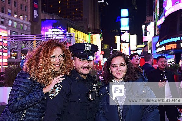 Policeman has his picture taken with tourists in Times Square  Manhattan  New York City  New York State  USA  North America