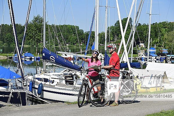 Paar mit E-Bikes im Hafen von Matzing am Wallersee  Salzburger Seenland  Salzburger Land  Österreich  Europa Paar mit E-Bikes im Hafen von Matzing am Wallersee, Salzburger Seenland, Salzburger Land, Österreich, Europa