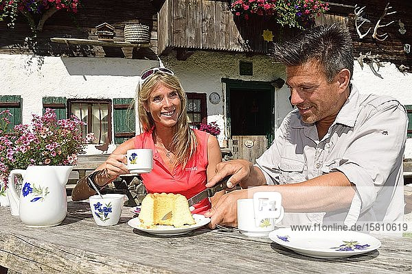 Hikers having a snack in front of the Chiemhauser Alm  Schleching  Chiemgau  Upper Bavaria  Bavaria  Germany  Europe