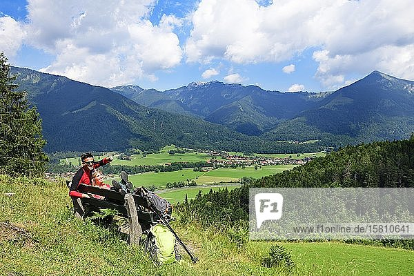 Hikers enjoy the view from alpine restaurant Streichen of Schleching and the Kampenwand  Chiemgau  Upper Bavaria  Bavaria  Germany  Europe