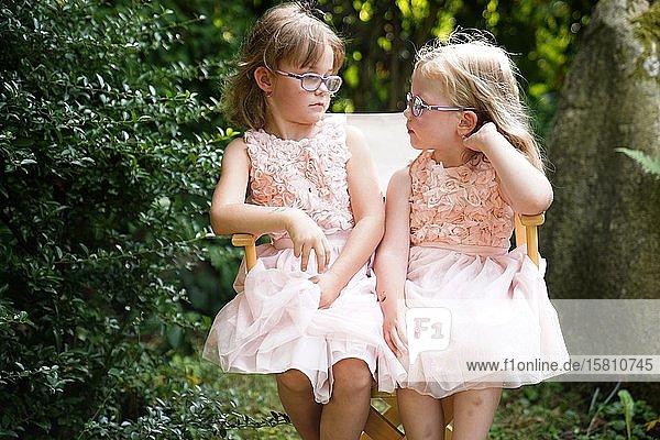 Portrait von zwei Schwestern  die zusammen auf einem Gartenstuhl sitzen (6 Jahre alt  3 Jahre alt)  Tschechien  Europa
