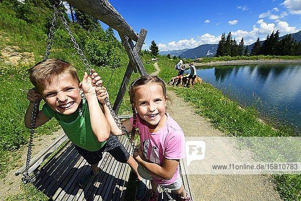 Familie spielt während einer Wanderung am Speichersee bei der Mittelstation  Hohe Salve  Hopfgarten  Brixental  Kitzbüheler Alpen  Tirol  Österreich  Europa