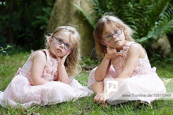 Zwei Schwestern sitzen im rosa Kleid im Garten (6 Jahre alt  3 Jahre alt) Tschechien