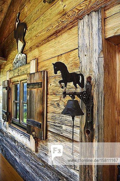 Kleine Zirbenholzhütte neben dem Berggasthof Streichen mit Glocke aus Schmiedeisen  Schleching  Chiemgau  Oberbayern  Bayern  Deutschland  Europa