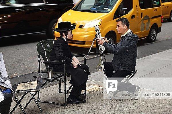 Ein jüdisch-orthodoxer Junge mit Schläfenlocken und Hut wird am Times Square von einem Straßenmaler porträtiert  Manhattan  New York City  New York State  USA  Nordamerika Ein jüdisch-orthodoxer Junge mit Schläfenlocken und Hut wird am Times Square von einem Straßenmaler porträtiert, Manhattan, New York City, New York State, USA, Nordamerika