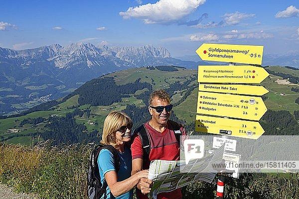 Wanderer auf dem Gipfelpanoramaweg der Hohen Salve beim Blick auf die Landkarte  Hopfgarten  Brixental  Kitzbüheler Alpen  Tirol  Österreich  Europa Wanderer auf dem Gipfelpanoramaweg der Hohen Salve beim Blick auf die Landkarte, Hopfgarten, Brixental, Kitzbüheler Alpen, Tirol, Österreich, Europa