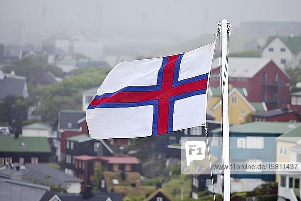 Flagge der Färöer vor Häusern im Nebel  Tórshavn  Streymoy  Färöer  Føroyar  Dänemark  Europa