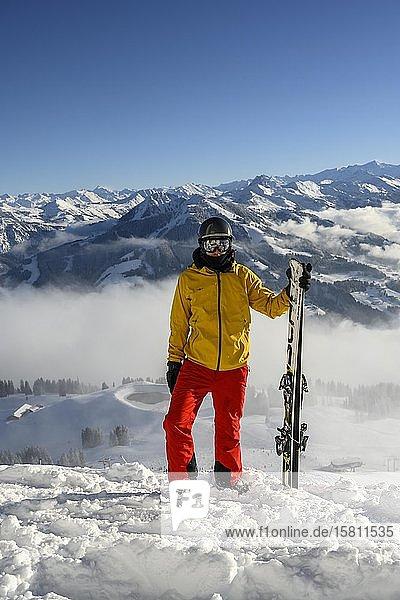 Skifahrer steht an der Skipste und hält Ski  Blick in die Kamera  verschneites Bergpanorama  Gipfel Hohe Salve  SkiWelt Wilder Kaiser Brixenthal  Hochbrixen  Tirol  Österreich  Europa