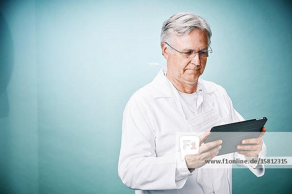 Grauhaariger Arzt mit Brille und Tablet-PC