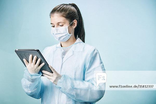 Ärztin mit Tablet-PC und Mundschutz