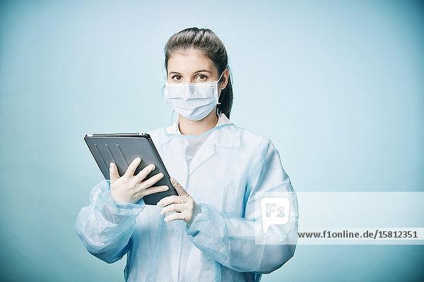 Ärztin mit Tablet-PC trägt Mundschutz und schaut ernst in Kamera