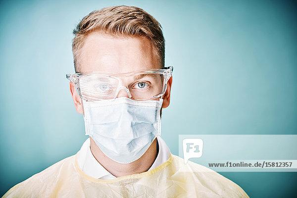 Junger Arzt mit Schutzbrille und Mundschutz