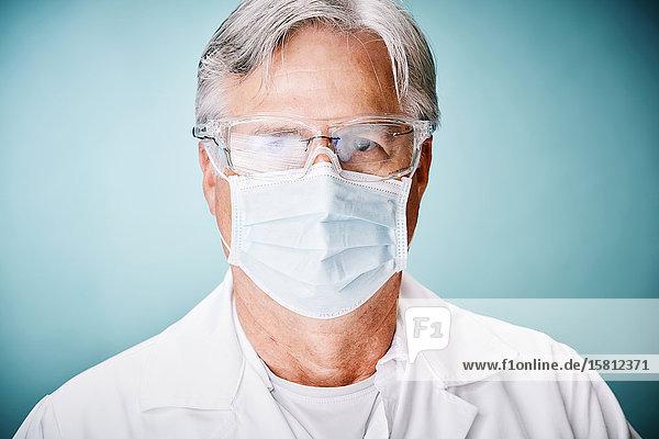 Grauhaariger Arzt mit Schutzbrille und Mundschutz