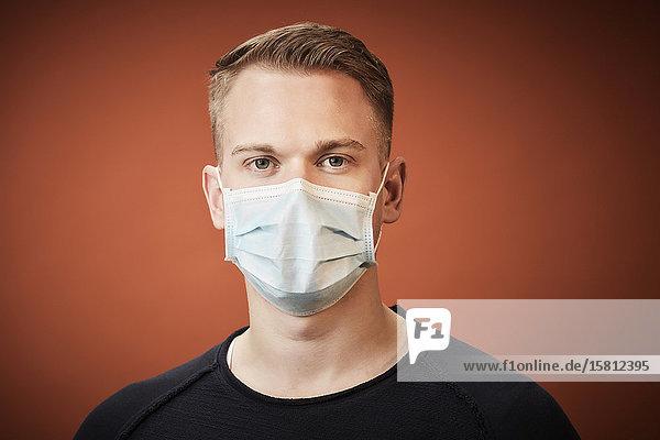 Junger Mann mit Mundschutz