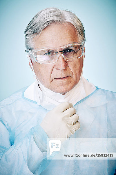 Grey-haired doctor with protective gloves and goggles and mouth guard pulled down