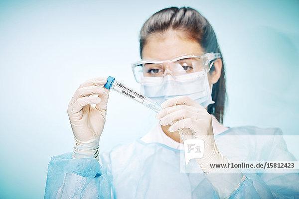 Laborantin mit Schutzbrille und Mundschutz hält Probe mit Coronavirus in Kamera