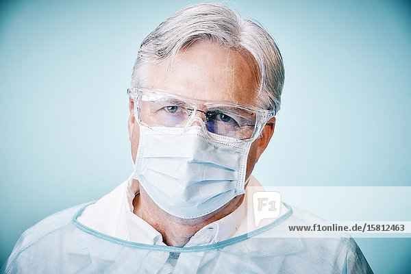 Doctor with goggles and face mask looks into camera