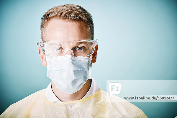 Young lab technician with protective goggles and face mask looks into the camera