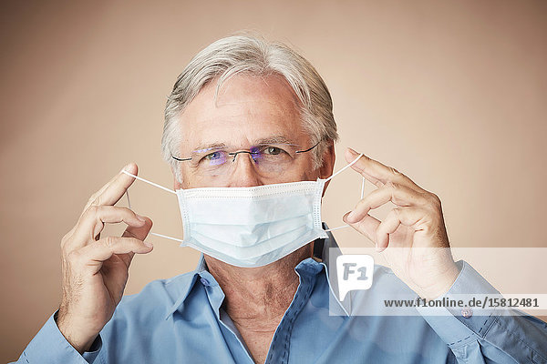 Grauhaariger Mann zieht Mundschutz hoch