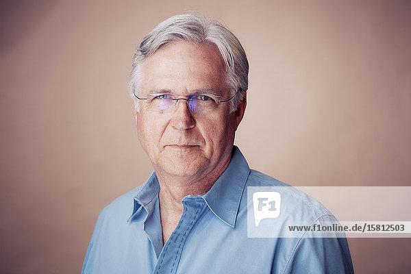 Grauhaariger Mann mit Brille und Hemd blickt in Kamera
