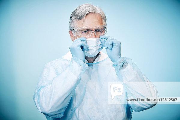 Grauhaariger Arzt mit Schutzhandschuhen und Schutzbrille zieht Mundschutz hoch